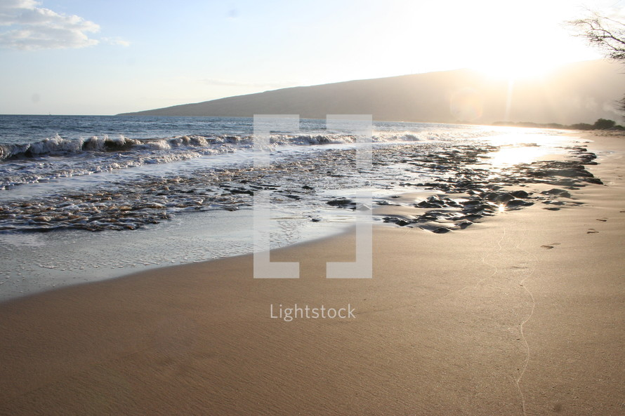 sunburst over waves rolling onto a beach