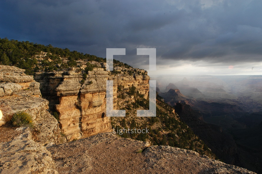 Mountain cliffs overlooking a deep canyon with dark storm clouds behind