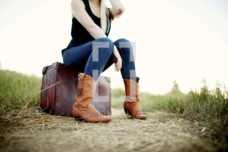 woman sitting on a suit case on a dirt road boots grass