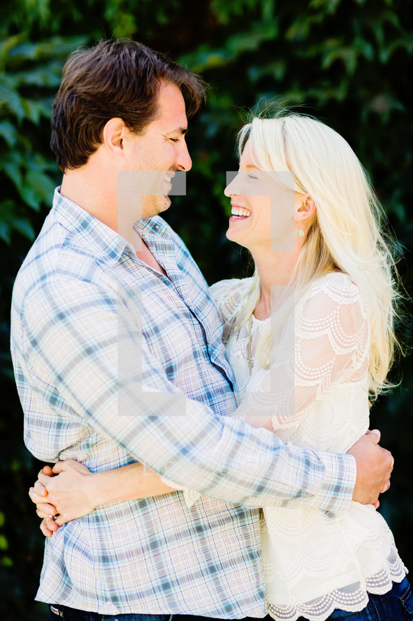 A man and woman smiling with arms around each other love engagement