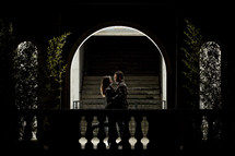 Couple embracing in lighted archway.