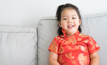 little girl in a traditional Chinese dress sitting on a couch