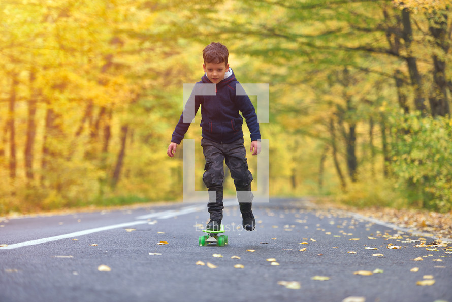 boy riding skateboard, outdoors in autumn environment on sunset warm light