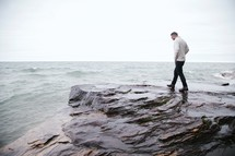 man walking on rocks near a shore