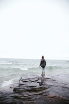 woman standing along rocks on a shore