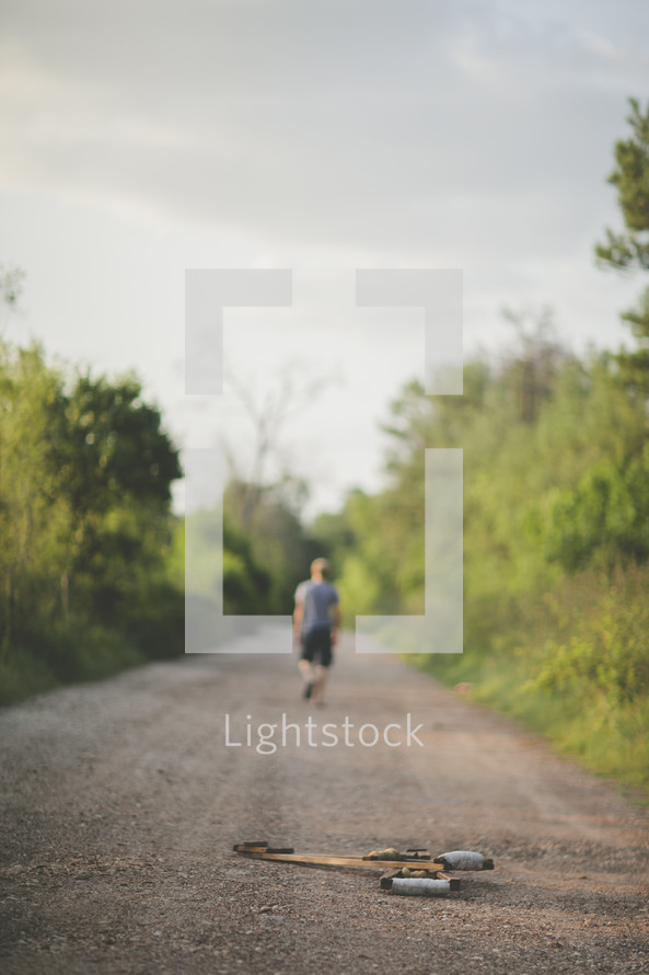 man walking down a dirt road