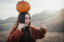 a woman with a pumpkin on her head