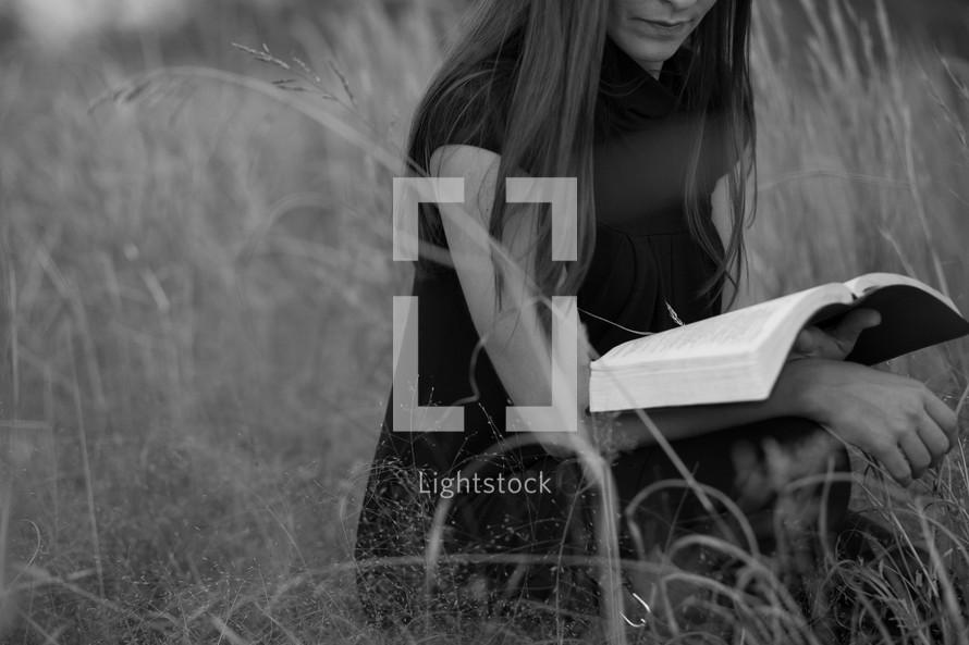 Woman reading Bible outdoors in an open field