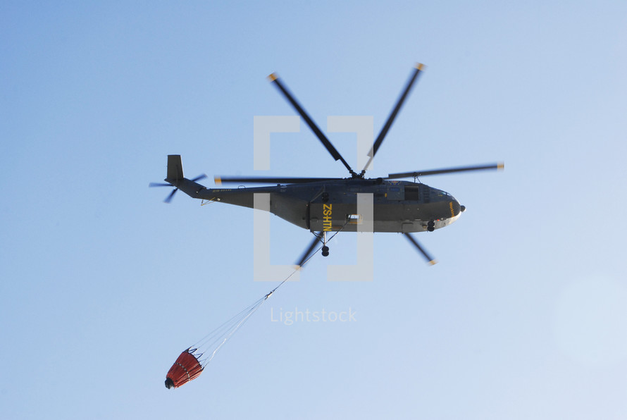 helicopter carrying a bucket of water for firefighting