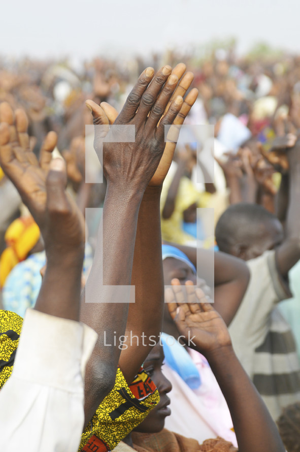 Crowd of Nigerian's lifting their hands in worship