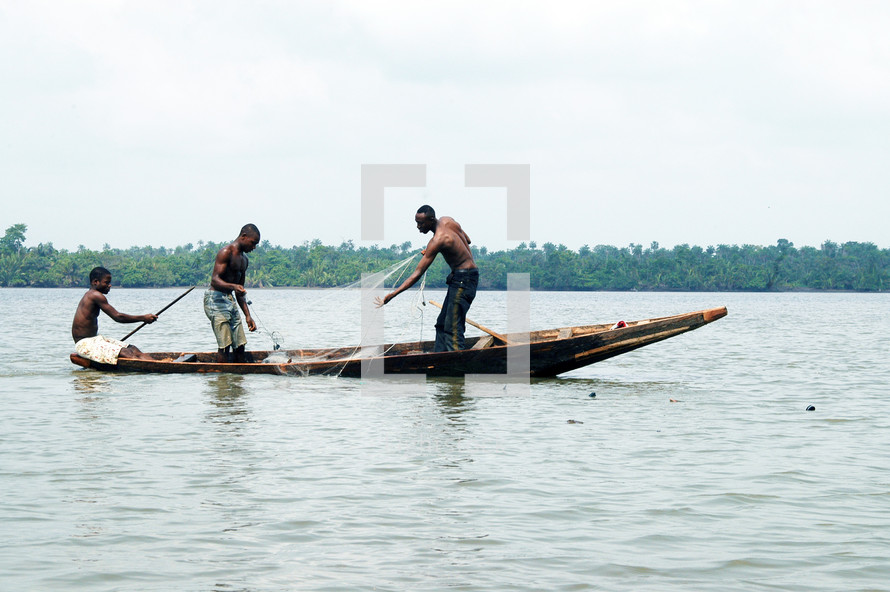 Three Nigerian's fishing on a small boat with a net