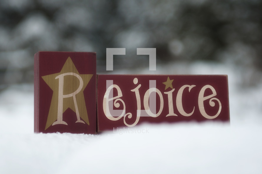 Rejoice wooden block in the snow.