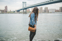 a woman with a purse walking along the shore in NYC