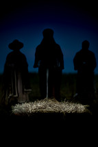 silhouettes of wisemen presenting gifts to baby Jesus