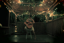 woman playing a guitar in a gazebo at night