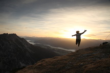 woman jumping for joy on a mountain top