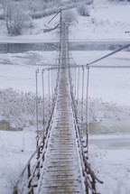 ice and snow on a swinging bridge over a river