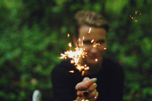 a woman holding out a sparkler