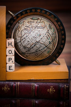 "A globe bookend and dice spelling ""hope"" on a leather Bible."