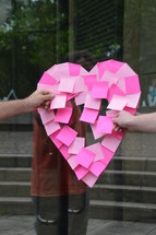 making a heart shape in sticky notes on a glass door