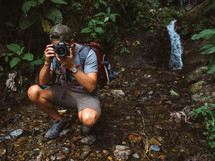 man taking a picture with a camera in a forest