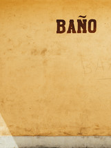 "A stucco wall with the word ""bano."""