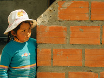 A boy stands at the end of an orange brick wall.