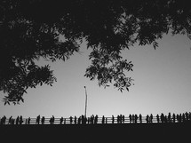 silhouettes of people on a bridge