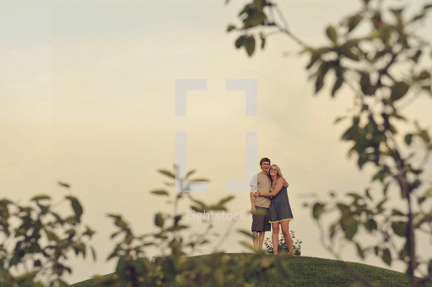 Embracing couple standing on a hilltop.