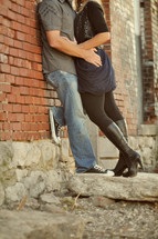 Embracing couple leaning against a brick wall.