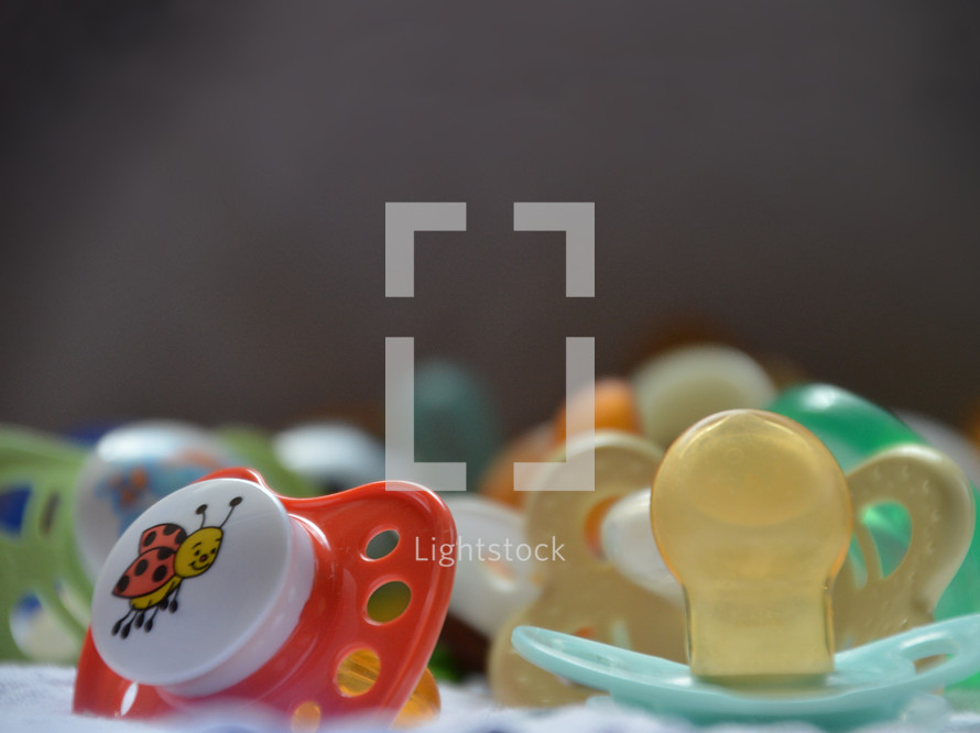 a bunch of pacifiers,  pacifier, dummy, comforter, baby, toodler, child, little, soother, lost, family, children, kid, kids, new, newborn, young, pacifiers, care, calm, soothe, lull, reassure, comfort, smooth, pacify, quiet, lot, bunch, cluster