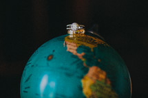Wedding rings on top of a globe.