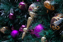 Purple and gold ball ornaments hanging from pine Christmas tree.