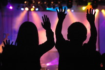 People in worship service with raised hands