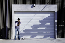 man standing with a soccer ball in front of a garage
