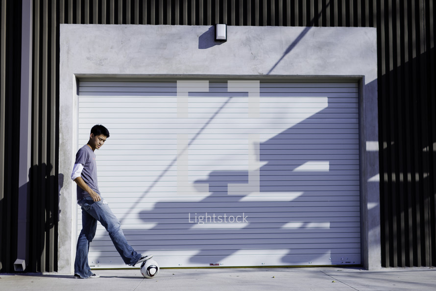 Boy standing outside closed garage door with foot on soccer ball.