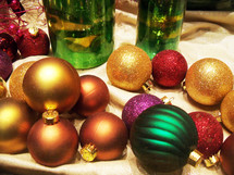 Gold, red and green Christmas ornaments decorate a window with colorful ornaments to add some Christmas cheer to the night air letting everyone in sight that Christmas time is here.