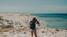 a woman in shorts and a backpack walking on a beach
