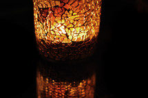 light from a burning candle through mosaic glass candle holder