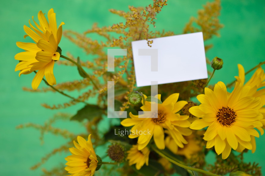 yellow flowers and a blank piece of white paper