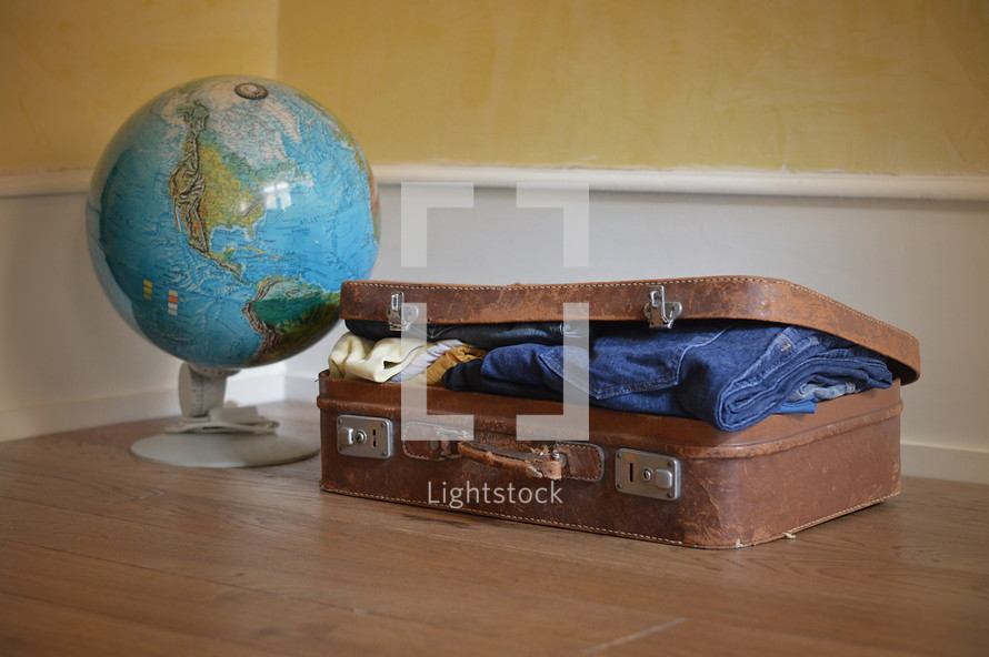 a globe and a packed suitcase