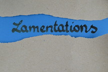 Lamentations - torn open kraft paper over blue paper with the name of the prophetic book Lamentations