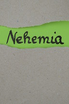 torn open kraft paper over green paper with the name of the book Nehemiah