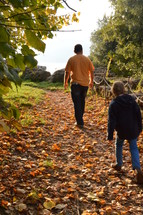 father and daughter walking on a path covered in fall leaves