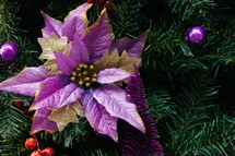 purple poinsettia ornament on a Christmas tree
