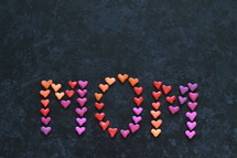 the word MOM written with many little colorful clay hearts on black background