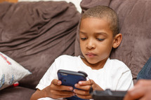 A boy playing a video game on a couch.
