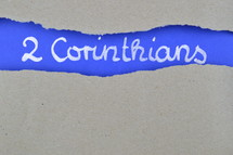 title 2 Corinthians exposed under gray torn paper