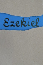 Ezekiel - torn open kraft paper over blue paper with the name of the prophetic book  Ezekiel
