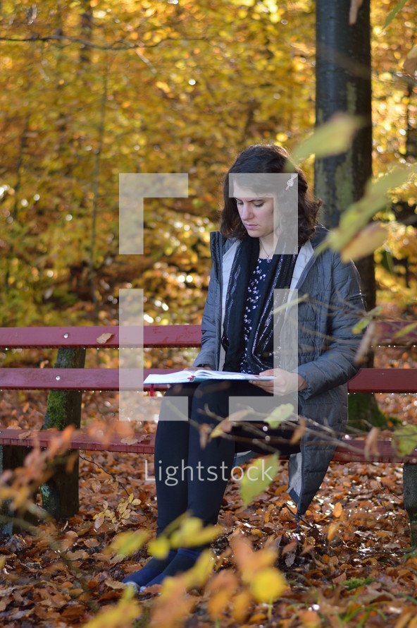a woman reading on a bench in a park in fall